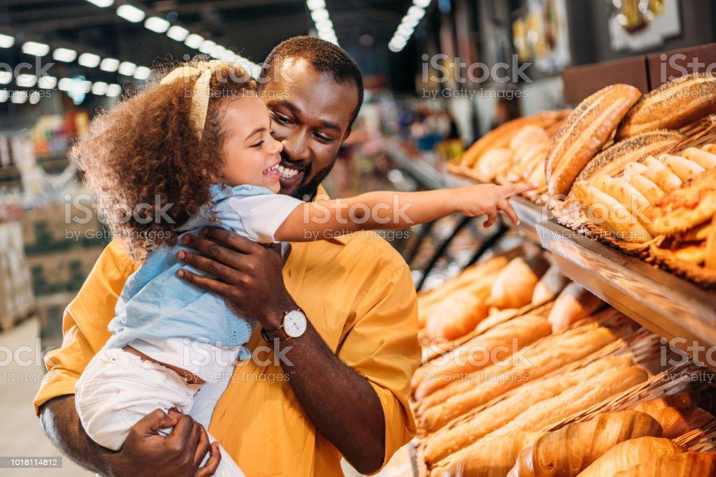 Afrikanische amerikanische kleines Kind zeigt mit dem Finger auf Gebäck Vater im Supermarkt – Foto