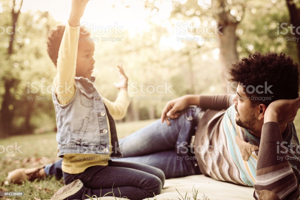 African American little girl and her father in forest having conversation. royalty-free stock photo