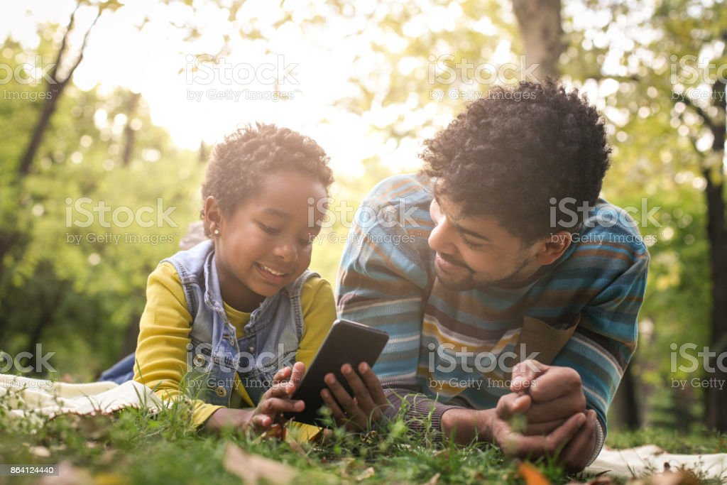 African American little girl and her father lying down in park and using mobile phone together. royalty-free stock photo