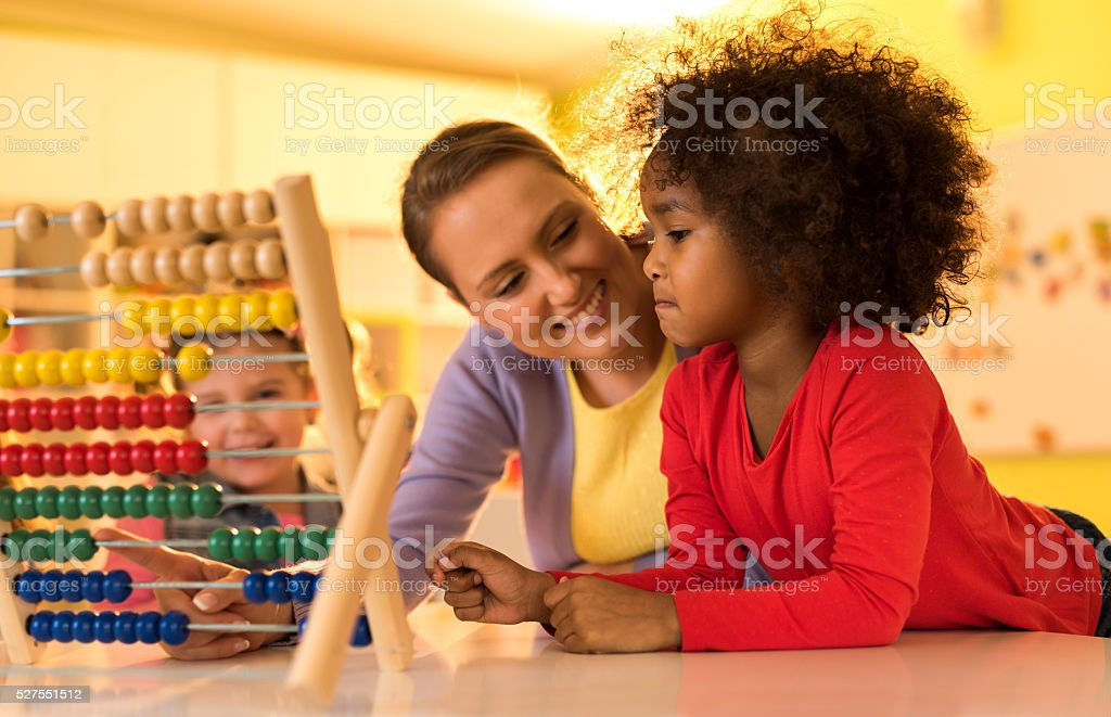 African American little girl and teacher using abacus at kindergarten. stock photo