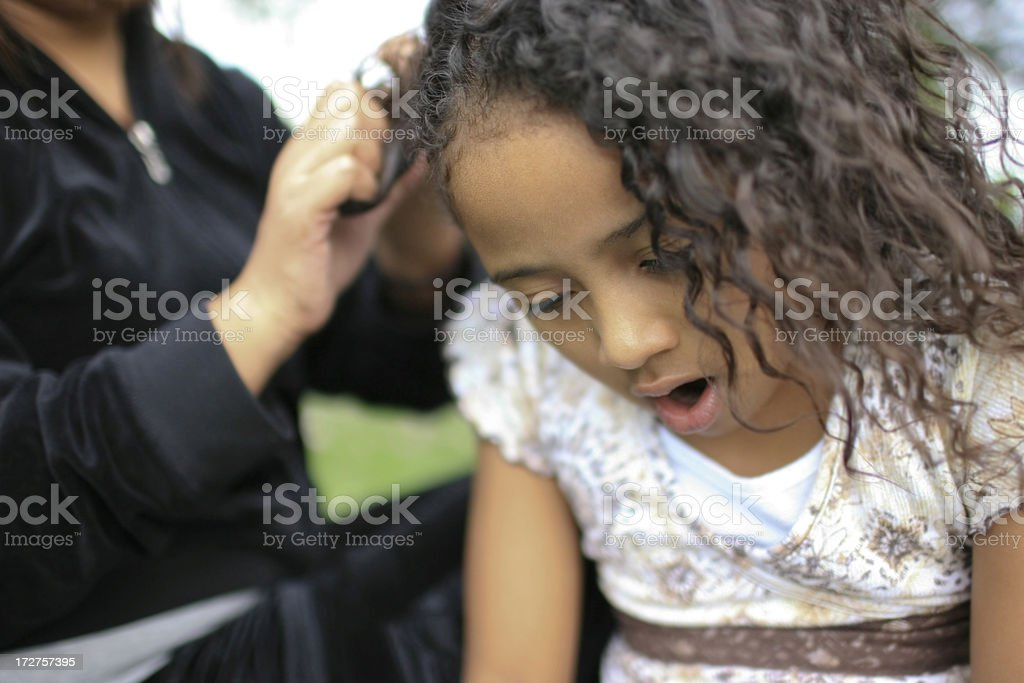 African American Little Girl in Pain, Mom Braiding Hair stock photo