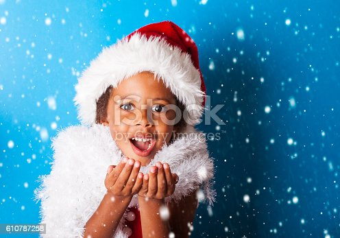 istock African American little girl in Santa Claus hat blowing snowflakes 610787258