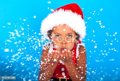 istock African American little girl in Santa Claus hat blowing snowflakes 610787290