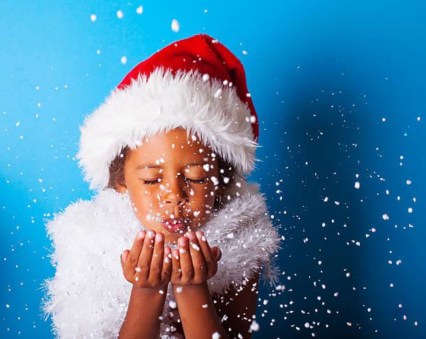 african american little girl in santa claus hat blowing snowflakes - gute winterjacken stock-fotos und bilder