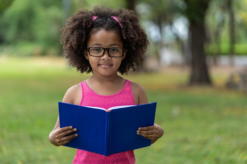African American little girl withcurly and hair wearing glasses while reading a book at summer outdoor. Education or Field trip concept