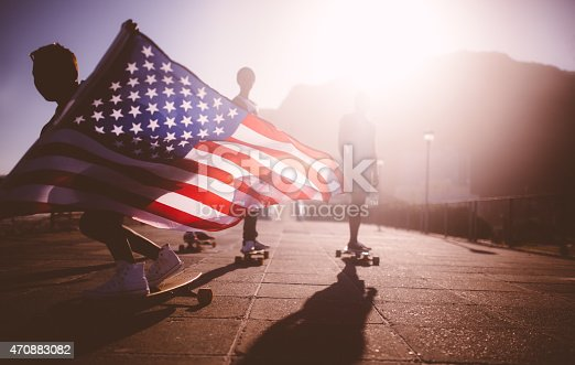Teenage African American skater flying an American flag past the camera
