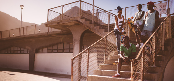 Group of African American longboarders in an urban setting looking cool