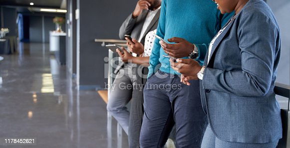 istock African American male and female coworkers holding their cellphones to surf the web together 1178452621