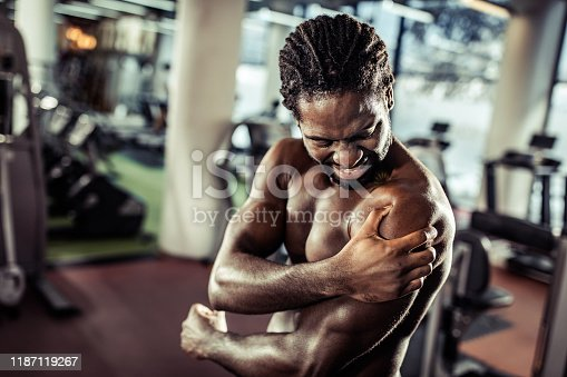 Muscular build black athlete injured his shoulder on sports training in a gym.