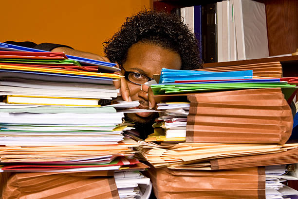 African American male buried behind a pile of folders stock photo