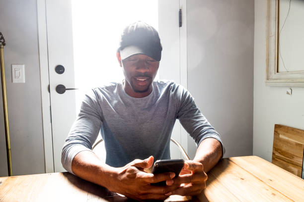 african american male checks his phone - apply online stock photos and pictures