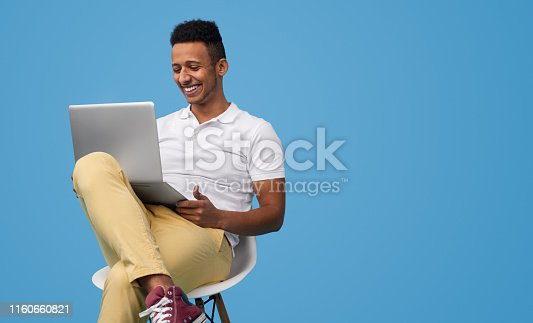 Handsome black student in casual outfit smiling and using laptop for homework while sitting on chair against blue background