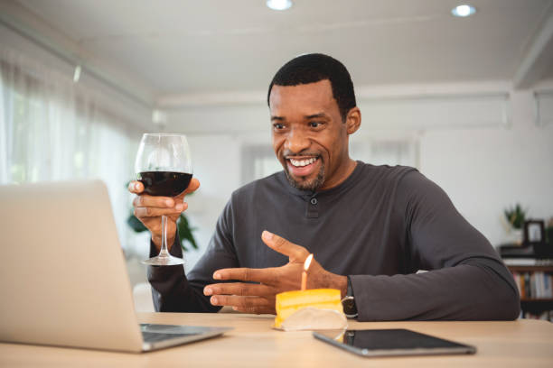 African American male doing online celebration with toasting red wine via video call on laptop stock photo