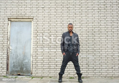 Portrait of an african american male fashion model standing outdoors in leather jacket