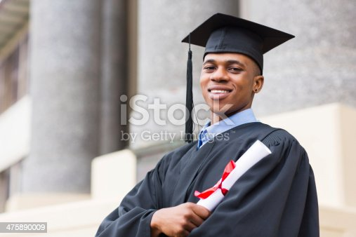 portrait of african american male graduate standing outside college