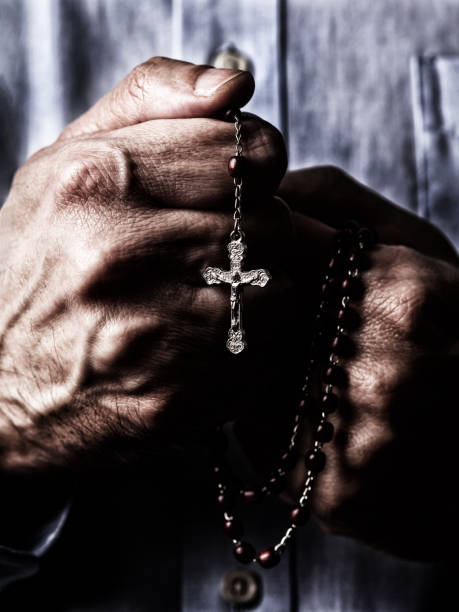 african american male hands praying holding a beads rosary with jesus christ in the cross or crucifix on black background. - african american church stock pictures, royalty-free photos & images