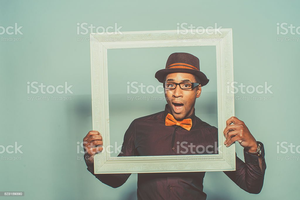 African American Male holding a white wooden frame stock photo