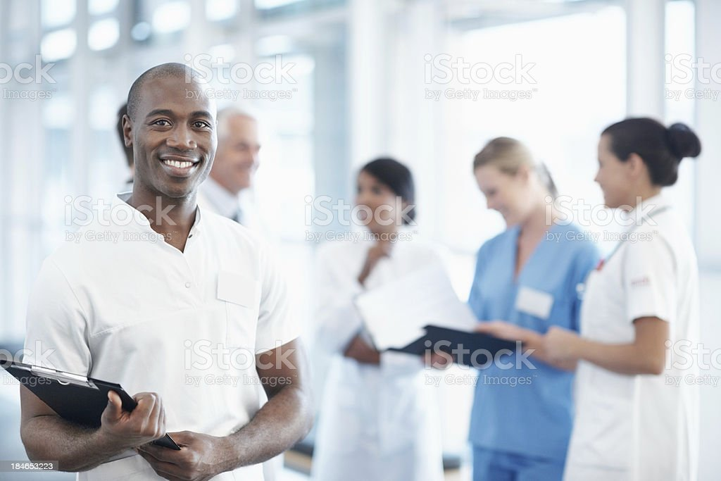 African American male nurse with medical team in the background stock photo