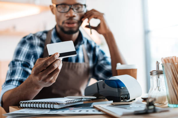 african american male owner working with credit card reader and smartphone in coffee shop - business credit card stock photos and pictures