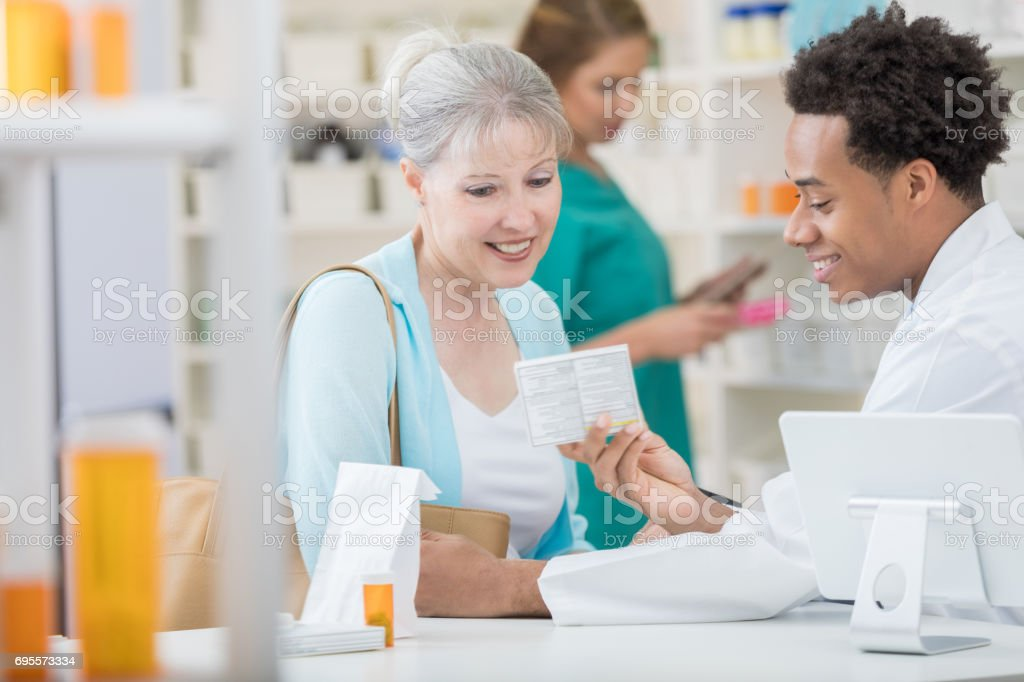 African American male pharmacist reviews medication with customer stock photo