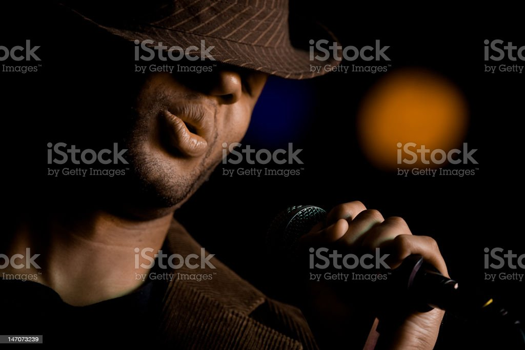 African American male singer wearing a fedora at microphone stock photo