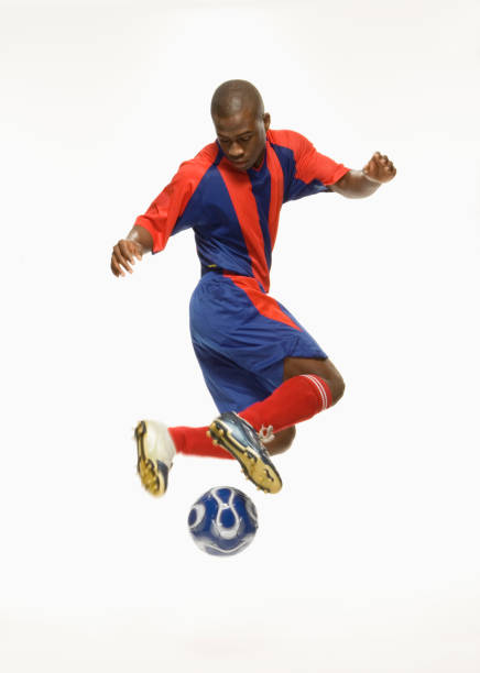 African American male soccer player kicking ball stock photo