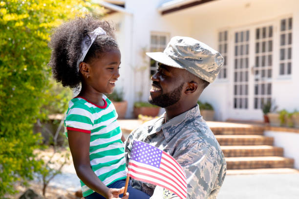 African American male soldier holding his daughter with a US flag in his arms African American male solider wearing uniform holding his daughter with a USA flag in his arms, standing by the house on a sunny day, smiling and interacting. family 4th of july stock pictures, royalty-free photos & images