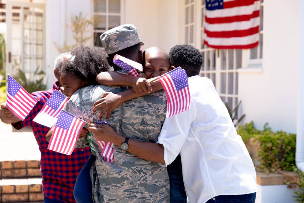 African American male soldier wearing uniform and his family standing by their house stock photo