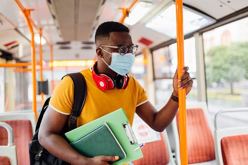 Young African American male student using a public bus to go around the city, wearing a protective face mask, carrying a backpack and books, going to a class