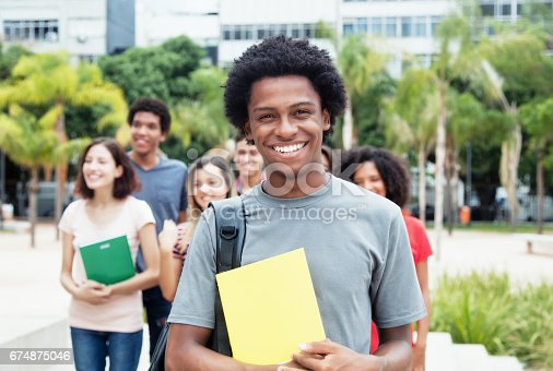 African american male student showing thumb with group of international students outdoor in the summer in the city