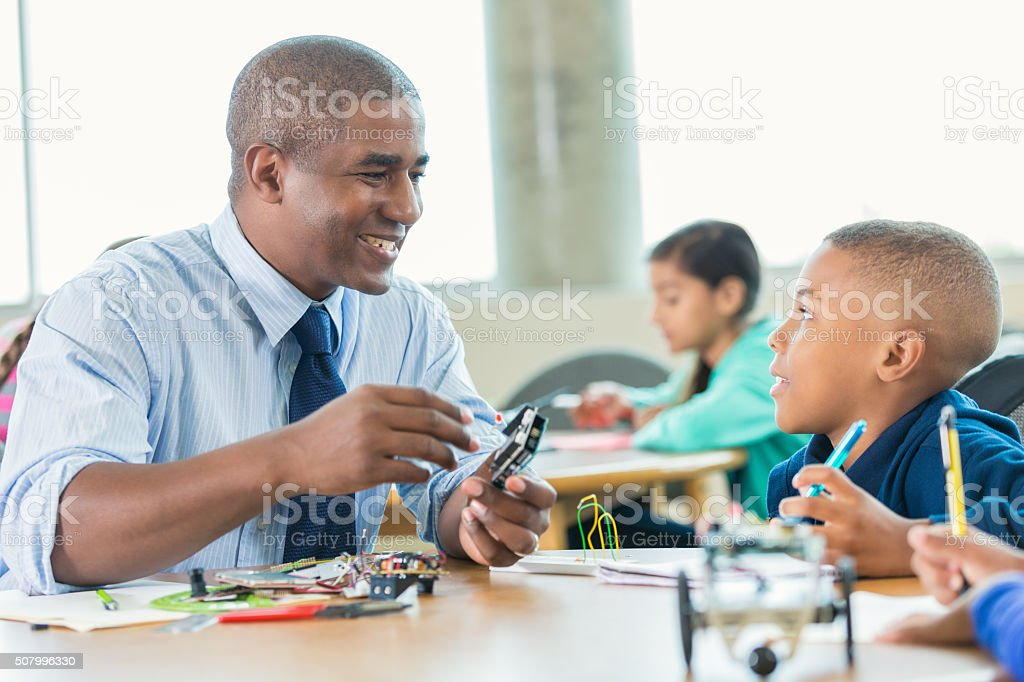 African American male teacher using robotics kit in elementary class stock photo
