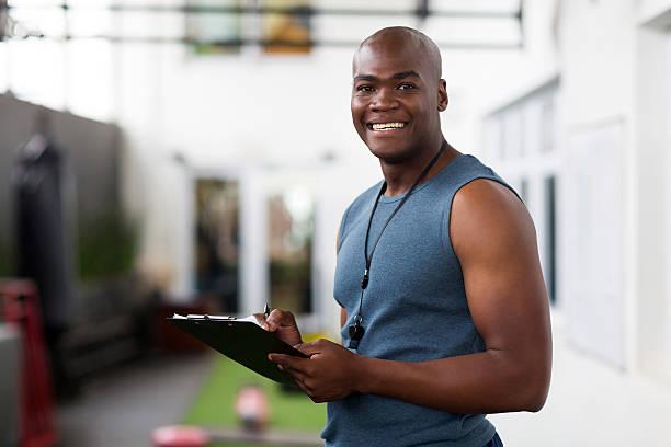 afroamericana con entrenador masculino con portapapeles - entrenador personal fotografías e imágenes de stock
