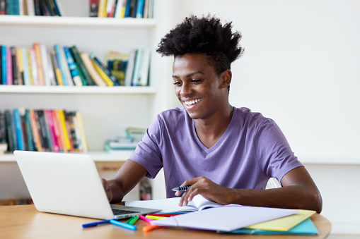 1127582480 istock photo African american male young adult streaming and watching clips and movies at computer 1218330655