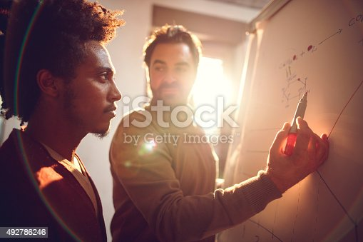 497812268 istock photo African American man and his colleague analyzing a chart. 492786246