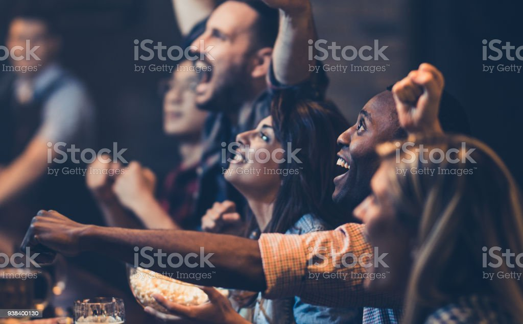 African American man and his friends cheering while watching a game in a bar. stock photo