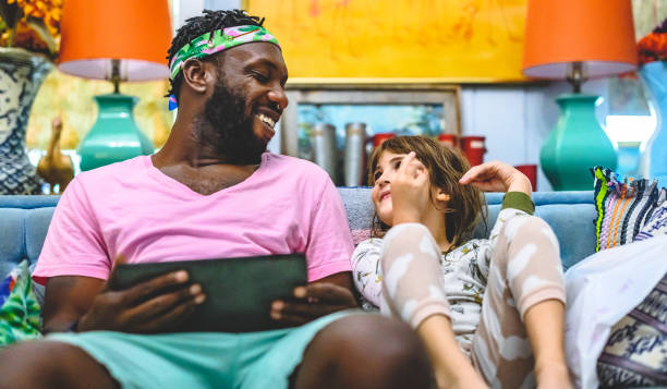 African American man and stepdaughter little girl child use a digital tablet at home together stock photo