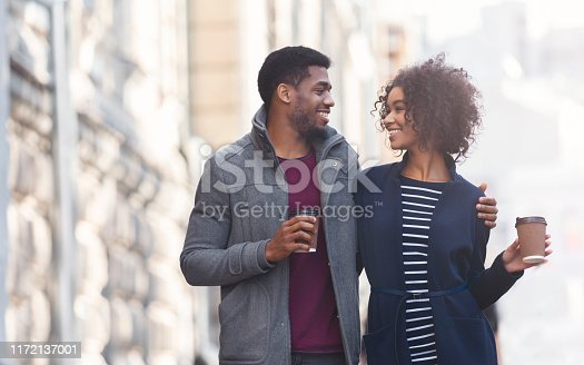 Couple date. Black man and woman drinking coffee outdoors, walking in the city, copy space