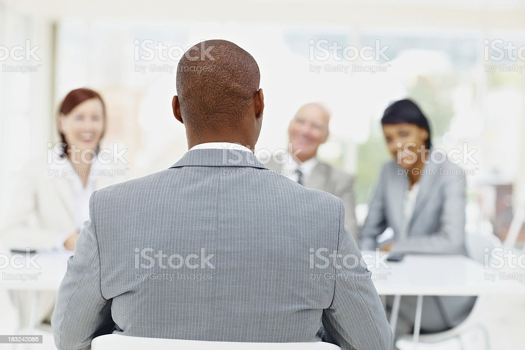 African American man being interviewed by business people stock photo