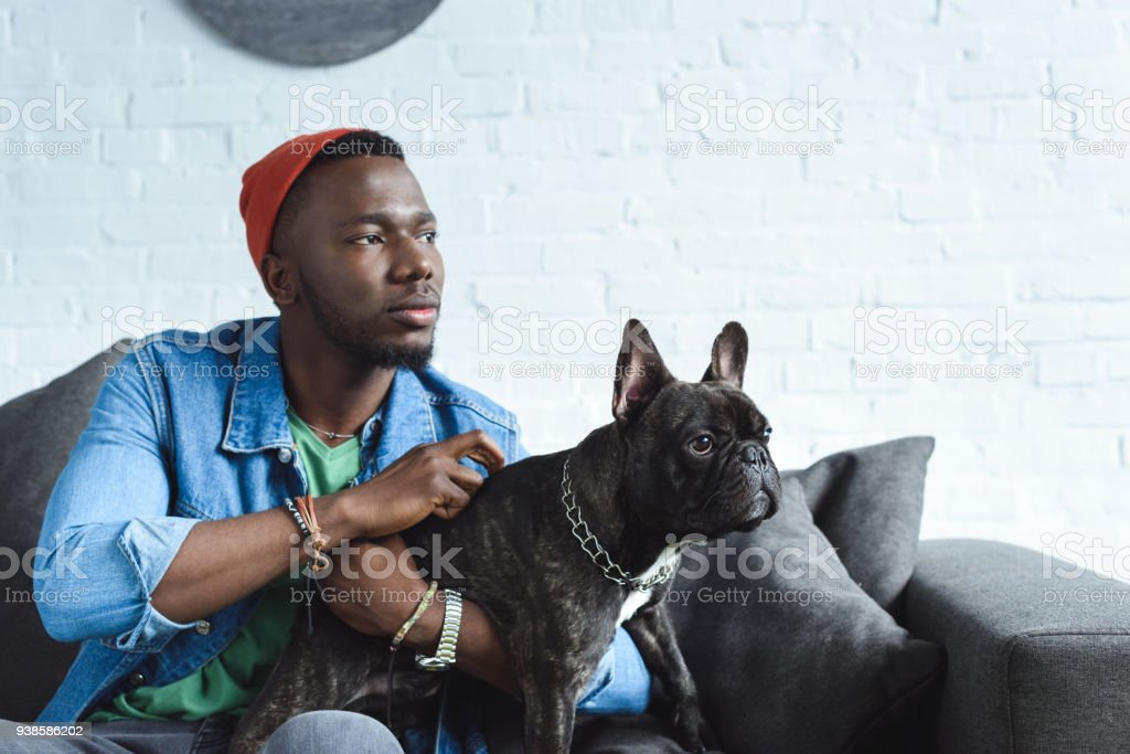 African american man cuddling black Frenchie on sofa stock photo