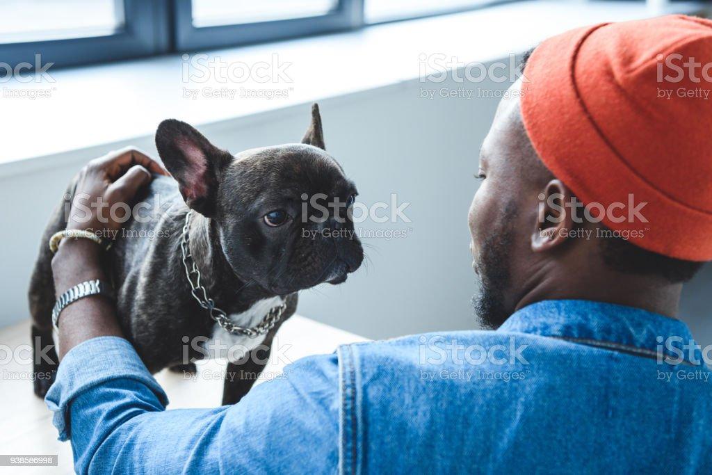 African american man cuddling cute French bulldog stock photo