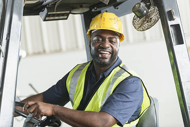 African American man driving a forklift stock photo