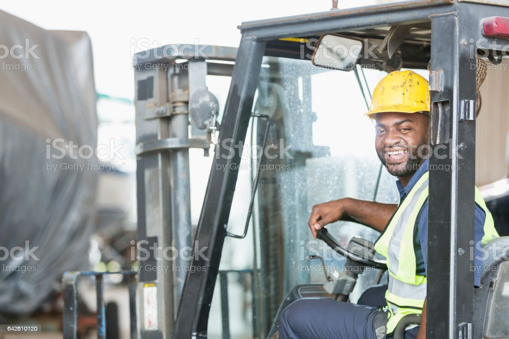 African American man driving forklift stock photo