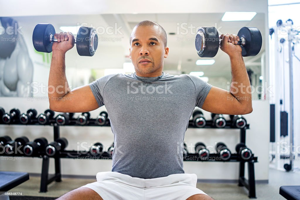 African American man exercising with dumbbells at gym. royalty-free stock photo
