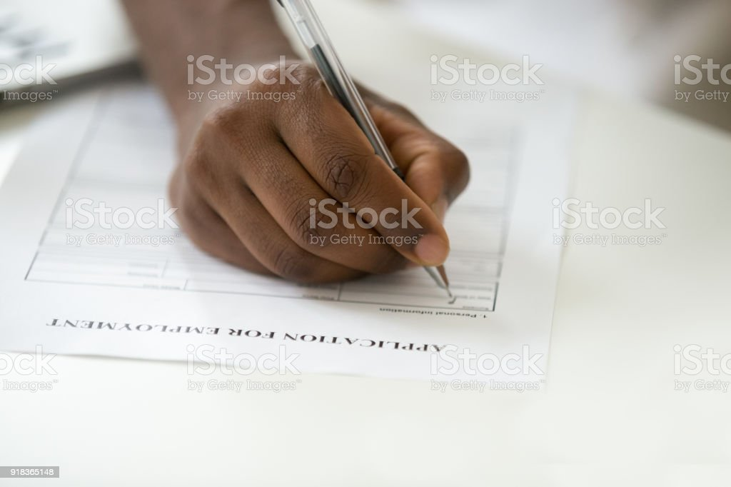African american man filling employment application form, close up view stock photo