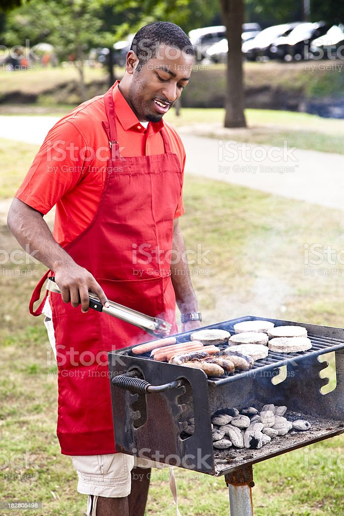 African American Man Grilling Burgers, Hot Dogs, and Sausages royalty-free stock photo