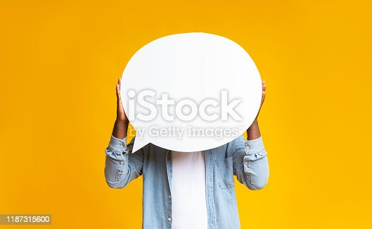 Unrecognizable black guy holding empty speech bubble in front of his head over yellow studio background, copy space