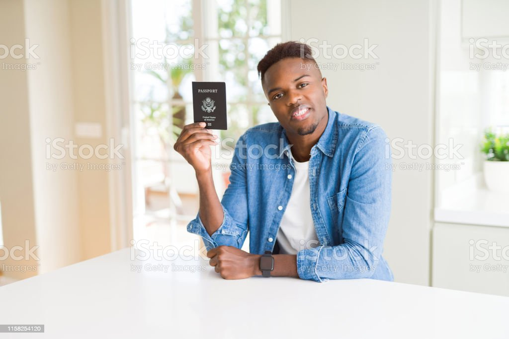 African american man holding passport of United States of America...