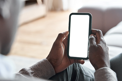 African american man holding smart phone with mockup white blank display, empty screen for app ads sitting on couch at home. Mobile applications technology concept, over shoulder close up view.