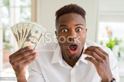 African american man holding twenty dollars bank notes scared in shock with a surprise face, afraid and excited with fear expression