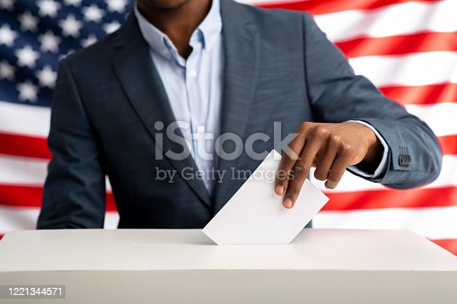 Election or referendum in America. African american man holds envelope in hand above vote ballot. USA flag on background.